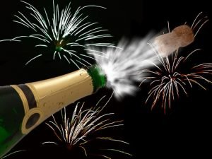 Champagne cork popping with fireworks in the background