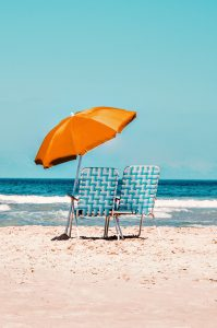 two blue beach chairs on the sand with an orange umbrella